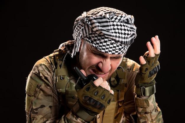 Soldat masculin en tenue de camouflage parlant à travers un talkie-walkie sur un mur noir