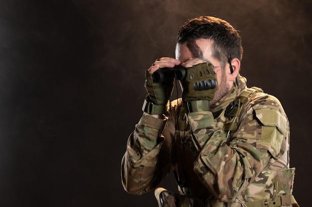 Soldat masculin en uniforme militaire regardant à travers des jumelles sur un mur sombre