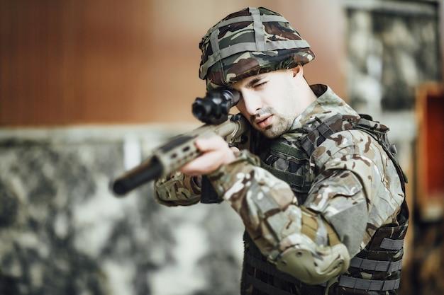 Un soldat militaire cible et tient un gros fusil dans le bâtiment