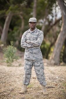 Soldat militaire debout avec les bras croisés dans le camp d'entraînement