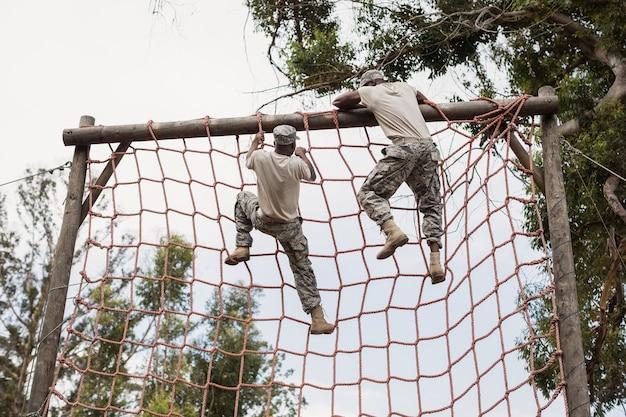 Soldat militaire escalade un filet pendant la course d'obstacles dans le camp d'entraînement
