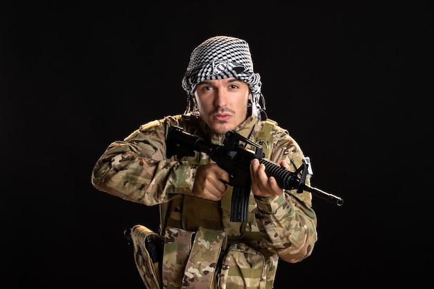 Soldat palestinien en camouflage combats avec mitrailleuse sur mur noir