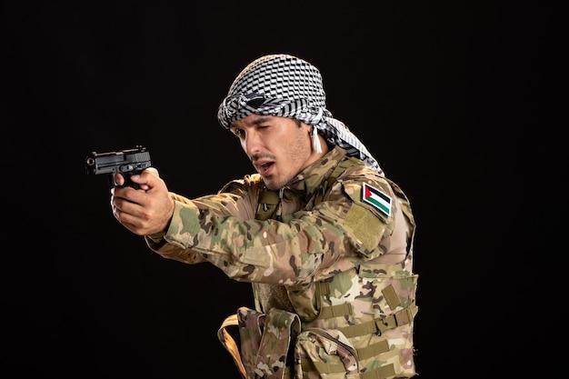 Soldat palestinien pointant son arme sur un mur noir