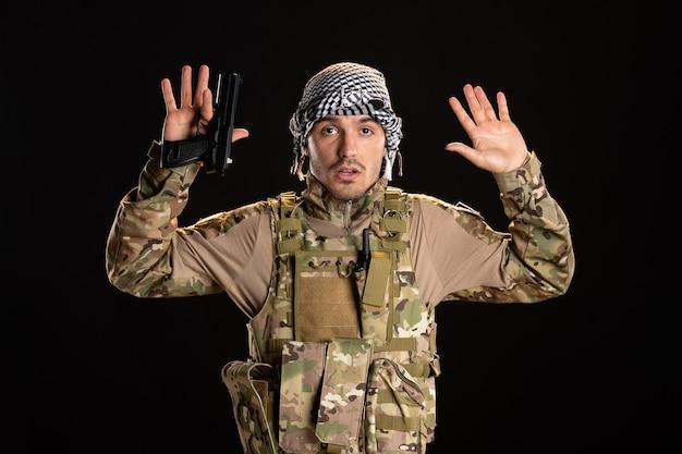 Soldat palestinien se rendant avec une arme à feu sur un mur noir