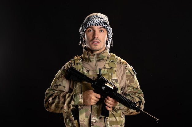 Soldat palestinien en tenue de camouflage avec mitrailleuse sur mur noir