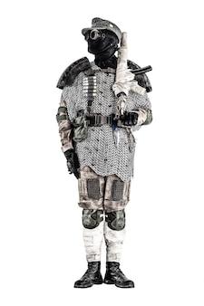 Soldat post-apocalyptique portant un masque et des lunettes noirs, une casquette de laine et une armure faite à la main à partir de pneus de voiture et d'haubert, au garde-à-vous avec une mitraillette sur l'épaule, isolé sur un tournage en studio blanc