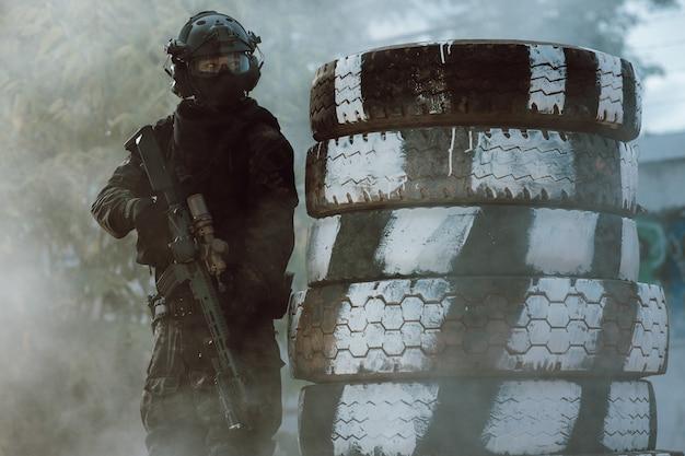 Soldat tenant un fusil sur le champ de bataille combat prêt. concept de style guerrier de combat au pistolet bb.