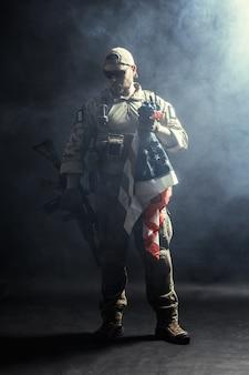 Soldat tenant une mitrailleuse avec drapeau national