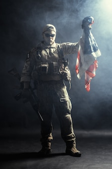 Soldat tenant une mitrailleuse avec le drapeau national