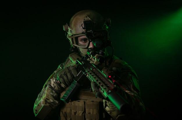 Le soldat en tenue militaire avec un appareil de vision nocturne et sur fond sombre