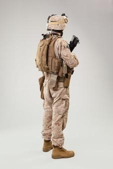 Soldat en uniforme de marine américain avec fusil sur gris clair, prise de vue en studio