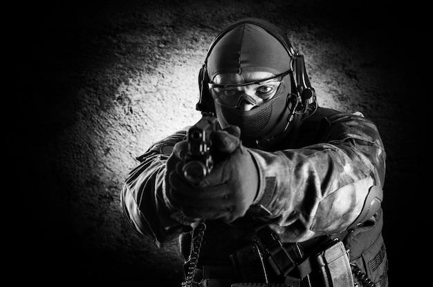 Un soldat de l'unité spéciale se tient avec un pistolet dans les mains et vise la cible. technique mixte