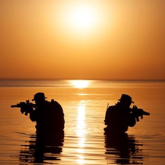 Les soldats de l'armée avec des fusils silhouette coucher de soleil orange en action lors de raid traversant la rivière dans l'eau