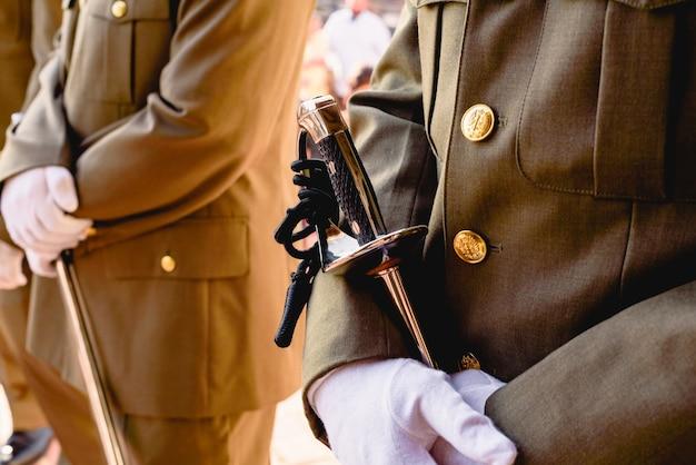 Les soldats de l'armée avec des gants tenant leurs sabres attendent d'être contrôlés par le supérieur