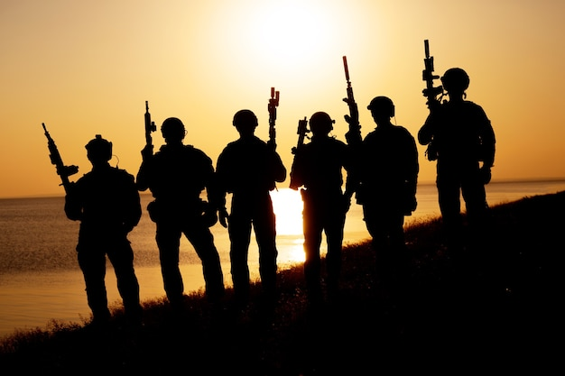 Soldats De L'armée Avec Silhouette Coucher De Soleil Orange Fusils Photo Premium