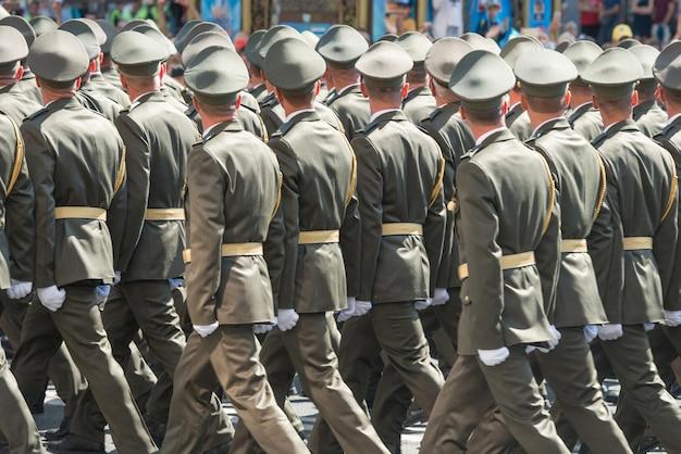 Soldats de l'armée en tenue de camouflage marchant sur un défilé militaire