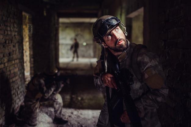 Soldats debout dans le couloir sombre du bâtiment vide. un barbu regarde et tient un fusil.