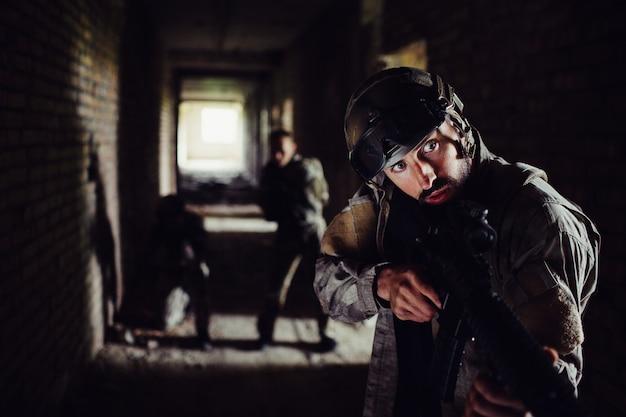 Des soldats sont debout dans un couloir sombre et attendent.
