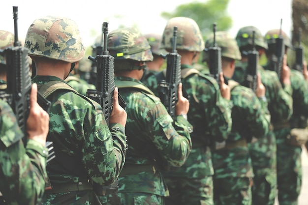 Les soldats sont en rang. arme à feu à la main. armée, bottes militaires, lignes de soldats commando.