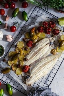 Sole de poisson grillée avec tomates cerises vertes et rouges, pomme de terre, câpres, ail, persil et huile d'olive
