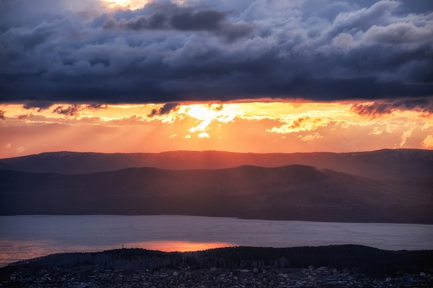 Le soleil approche de l'horizon dans les montagnes du sud de l'oural et le lac gelé turgoyak