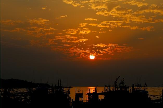 Le soleil avant le coucher du soleil sur le bateau de pêcheur en thaïlande