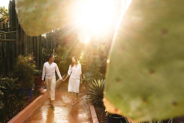 Le soleil brille sur un couple dans les clôtures blanches marchant autour du jardin botanique dans la ville africaine