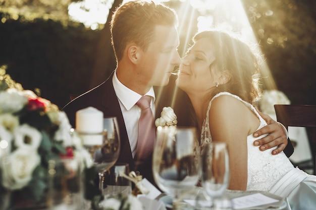 Le soleil brille sur couple de mariage étreignant à la table du dîner à l'extérieur