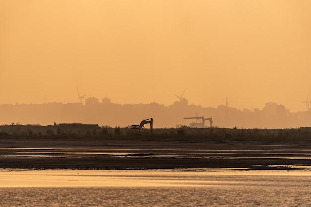 Le soleil brille d'or sur le chantier de construction le matin et une excavatrice travaille