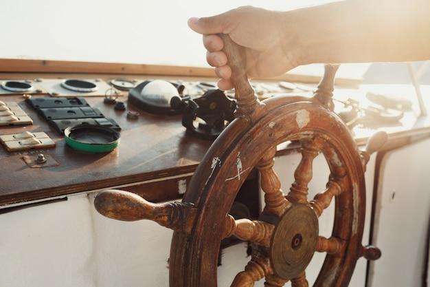 Le soleil brille sur la roue en bois tenue par l'homme