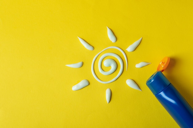 Soleil en crème solaire et bouteille de crème sur jaune