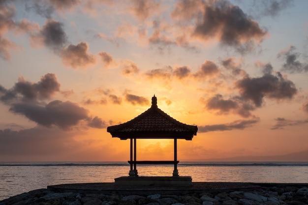 Soleil dans le pavillon sur la jetée au littoral au matin