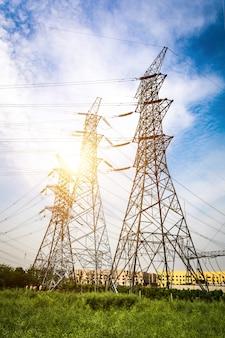 Soleil derrière la silhouette des pylônes électriques