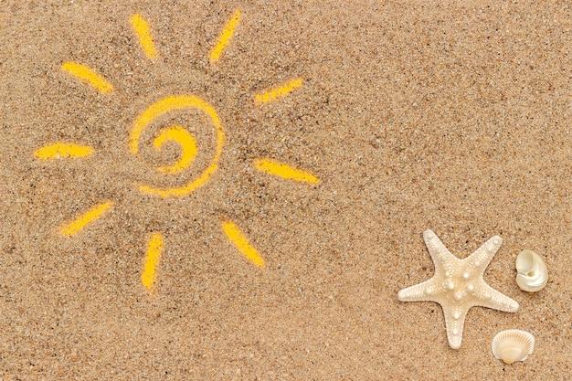 Soleil dessiné et étoile de mer, coquillages sur le sable