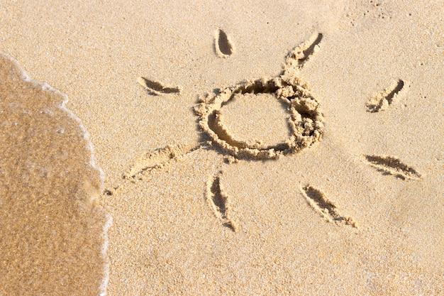 Soleil dessiné sur la plage de sable de la station pendant les vacances d'été. le symbole du soleil qui dessine sur le sable. fond se bouchent.