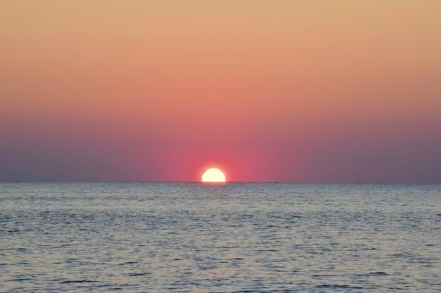 Le soleil du matin se levait à moitié de la mer calme.