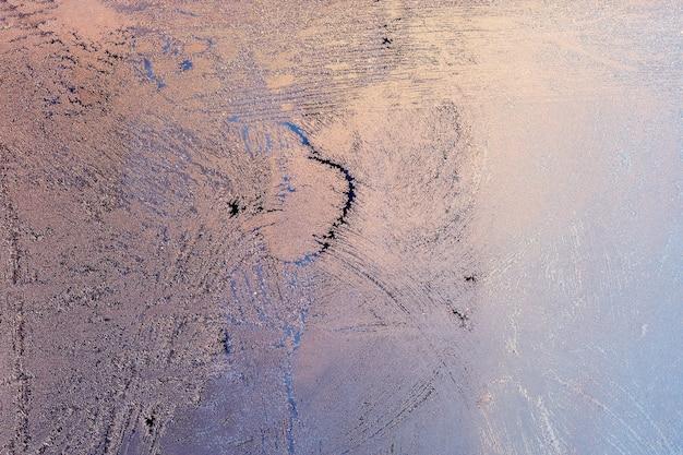 Soleil du soir et ciel bleu vif à travers le motif de givre sur une fenêtre