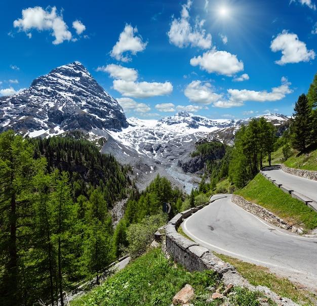 Soleil d'été col du stelvio avec forêt de sapins et neige au sommet de la montagne (italie). deux clichés piquent l'image.