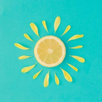 Soleil fait de pétales de fleurs de citron et jaune sur fond bleu clair. concept minimal d'été de fruits.