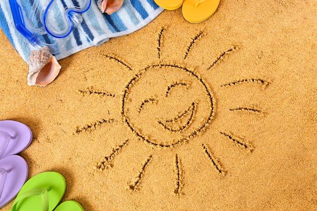 Le soleil heureux dessiné dans le sable