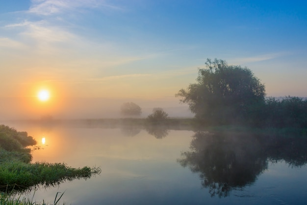Soleil orange sur la surface de la rivière avec du brouillard en matinée d'été. paysage fluvial