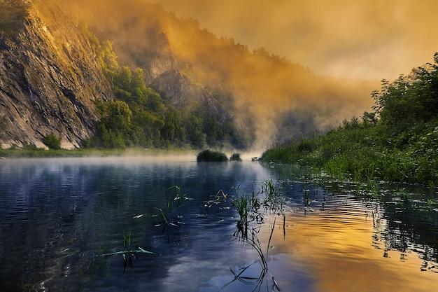 Le soleil a peint le brouillard du matin sur la rivière dans des couleurs vives.