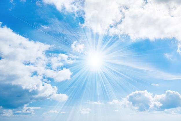 Soleil avec rayons sur ciel bleu avec nuages blancs