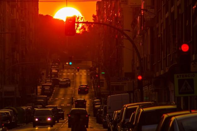 Le soleil rouge dans un coucher de soleil automnal illuminant les rues de la ville