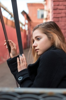Solitaire jeune fille en manteau noir, assis dans les escaliers avec fond urbain vintage. notion de solitude.