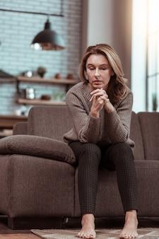Solitaire et triste. femme divorcée se sentant seule et triste assise sur le canapé tout en étant seule à la maison