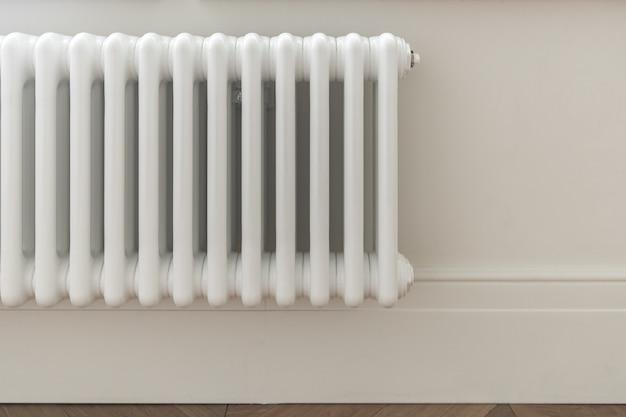 Solution élégante de la conception du système de chauffage domestique. radiateur court vertical monté sur un mur blanc, décoré d'une plinthe blanche.