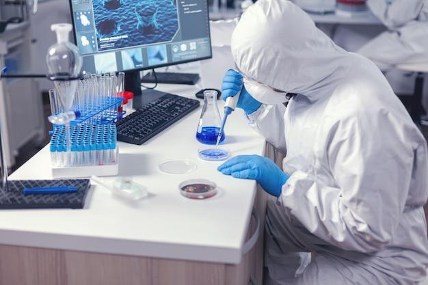 Solution de pipetage d'un technicien de laboratoire ciblé dans une boîte de pétri travaillant sur son lieu de travail dans un laboratoire moderne. chimiste dans un laboratoire moderne faisant des recherches à l'aide d'un distributeur pendant l'épidémie mondiale de covid-19.