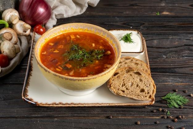 Solyanka - soupe traditionnelle russe à base de légumes, de bacon et d'herbes dans une assiette en céramique avec de la crème sure et du pain de seigle