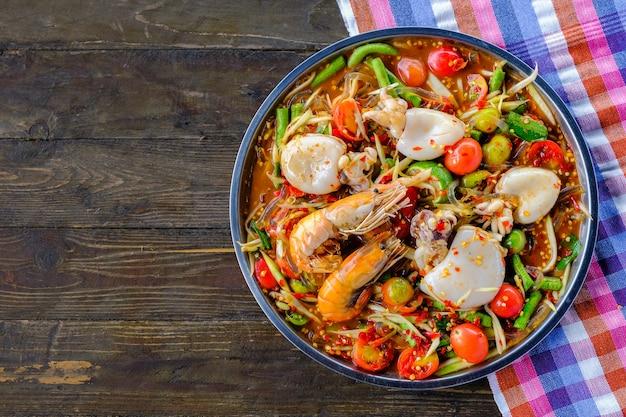 Som tam seafood (salade de papaye épicée) au crabe salé, sur une table en bois